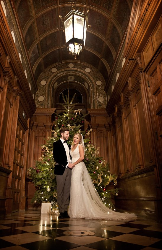 Bride and groom wedding at Luton Hoo in winter in front of christmas tree